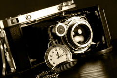 Retro camera and pocket watch. Old retro camera and pocket watch on black background. Vintage camera closeup Stock Image