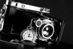 Retro camera and pocket watch. Old retro camera and pocket watch on black background. Vintage camera closeup Stock Photo