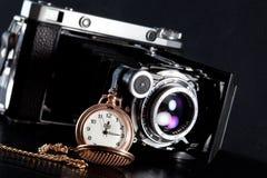 Retro camera and pocket watch. Old retro camera and pocket watch on black background. Vintage camera closeup Stock Images