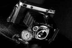 Retro camera and pocket watch. Old retro camera and pocket watch on black background. Vintage camera closeup Royalty Free Stock Image