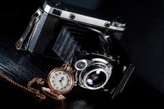 Retro camera and pocket watch. Old retro camera and pocket watch on black background. Vintage camera closeup Stock Photos