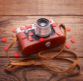 Retro Camera with red hearts on wooden background Stock Image