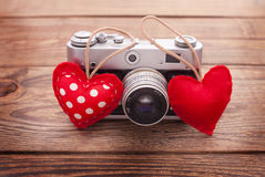 Retro Camera with red hearts on wooden background. Stock Images