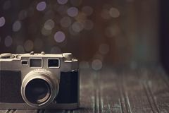 Retro camera on rustic background. An old fashioned retro range finder camera on rustic dark background with bokeh background Royalty Free Stock Photo