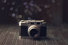Retro camera on rustic background. An old fashioned retro range finder camera on rustic dark background with bokeh background Stock Photography