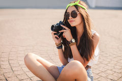 Retro camera shoots girl in the streets of the city. Stock Photo