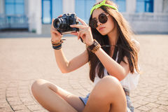 Retro camera shoots girl in the streets of the city. Royalty Free Stock Image