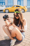 Retro camera shoots girl in the streets of the city. Stock Photos