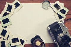 Retro camera and some old photos on wooden table. Vintage look stock photography