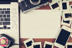 Retro camera and some old photos on wooden table. Vintage look Stock Image