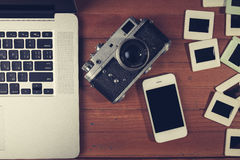 Retro camera and some old photos on wooden table. Royalty Free Stock Photos