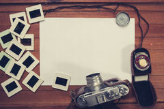 Retro camera and some old photos on wooden table. Vintage look Stock Images