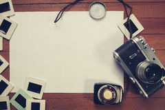 Retro camera and some old photos on wooden table Stock Photography