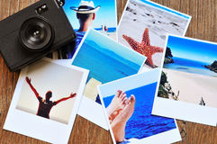 Retro camera and some photos on a wooden surface Stock Photos