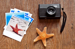 Retro camera, starfish and some photos on a wooden surface Stock Photos
