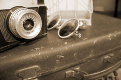 Retro camera, sunglasses and suitcase in sepia Stock Photography