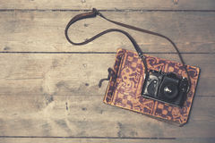 Retro camera with vintage photo album on wooden background Royalty Free Stock Photo