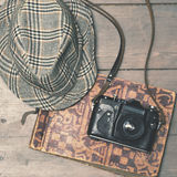 Retro camera with vintage trilby hat and photo album on wooden b Stock Photo