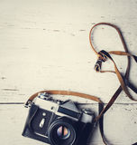 Retro camera on white wooden table Royalty Free Stock Images