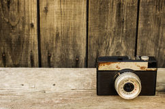 Retro camera on wood table background. Old rust hue Stock Photo