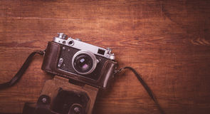 Retro camera on wood table background vintage color tone Royalty Free Stock Image