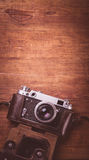 Retro camera on wood table background vintage color tone Royalty Free Stock Photos