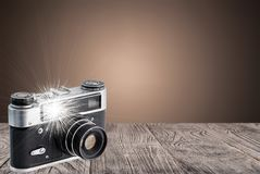 Retro camera on a wooden surface with flash royalty free stock image