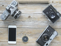 Retro cameras, compass and smartphone. On a wooden planks stock photo