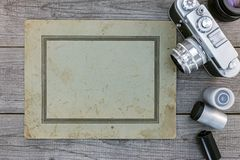 Retro cameras, lenses, negative film and old paper on wooden sur. Face, old memories Stock Photo