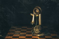 Retro candlestick telephone set on a chess game photography wit royalty free stock image