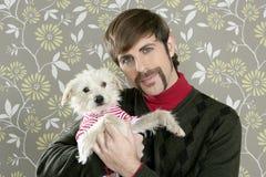 Retro cane della holding dell'uomo del disadattato sciocco sulla carta da parati Immagine Stock Libera da Diritti