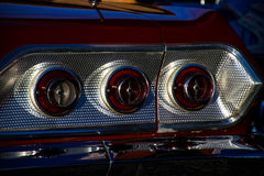 Retro Car Brake Lights or Tail Lights. On a classic hot rod. 3 circles of patterned brake lights with red paint job and chrome trim , with a fresh silver chrome stock photography