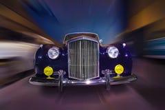 Retro car moves on city street Royalty Free Stock Photography