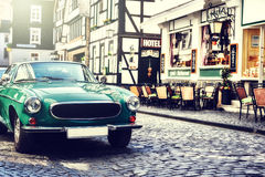 Retro car parked in old European city street. Copy space stock image