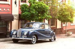Retro car parked in old European city street Stock Photos
