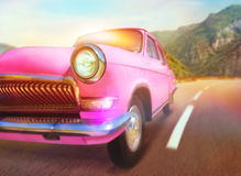 Retro car. Pink retro car on the road in mountains Royalty Free Stock Photos