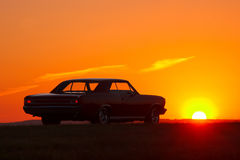 Retro car silhouette on sunset at summertime 1960s Stock Photography
