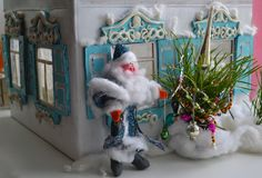 Photo of old house in Russian style, Father Frost and New Year tree. Retro card of small wooden house and plasticine Santa with fir Royalty Free Stock Image