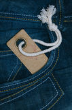 Retro cardboard paper tag with string in denim jeans pocket Royalty Free Stock Photo