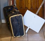 Retro cardboard suitcase and a blank placard outside an open door stock images