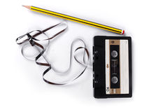 Retro cassette with loose tape and a pencil. To rewind over a white background royalty free stock photo