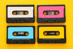 Retro cassette tape collection over yellow wooden table. top view. copy space.  royalty free stock images