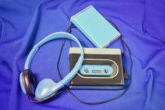 Retro cassette walkman on the blue fabric background. Retro walkman, headphones and cassette cover on the blue fabric background Stock Photography