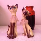 Retro cat statues with orange vase. Vintage siamese cat ceramic statues with a West German midcentury vase Royalty Free Stock Photos