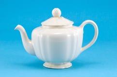 Retro ceramic white teapot dish on blue background Royalty Free Stock Image