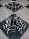 Retro chair on black and white checkered floor Stock Photos