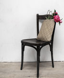 Retro chair in empty room with straw bag and flowers Stock Photography