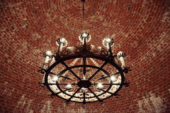 Retro chandelier in the brick ceiling Stock Photos