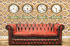 Retro chesterfield sofa with world time clocks on a wall. With vintage wallpaper Royalty Free Stock Photography