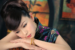 Retro Chinese Woman. A beautiful, young Chinese woman in a stylish retro 50s pose with her chin on her hands in deep contemplation Stock Photography